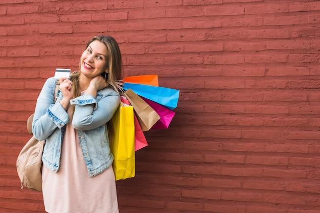 Glückliche frau, die mit einkaufstaschen und kreditkarte an der backsteinmauer steht
