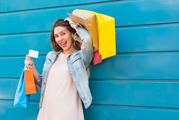 Glückliche frau, die mit einkaufstaschen und kreditkarte steht