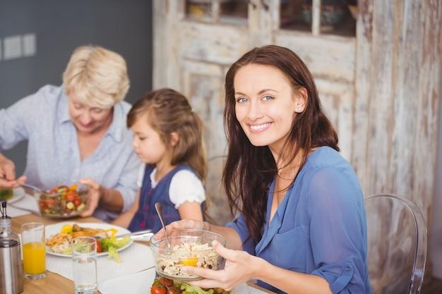 Glückliche frau, die mit familie frühstückt