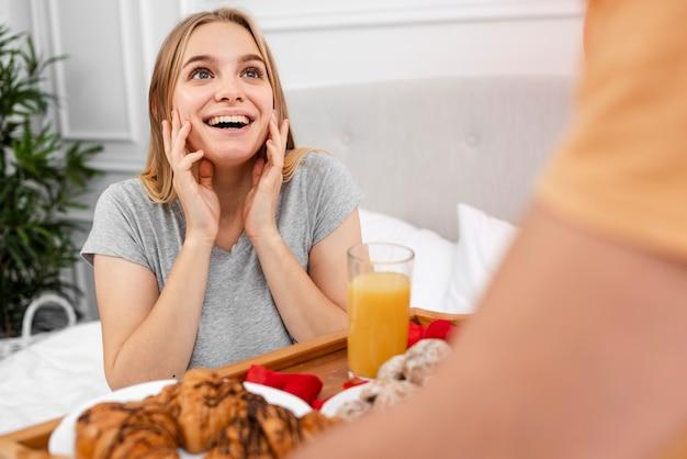 Glückliche frau, die mit frühstück im bett überrascht wird