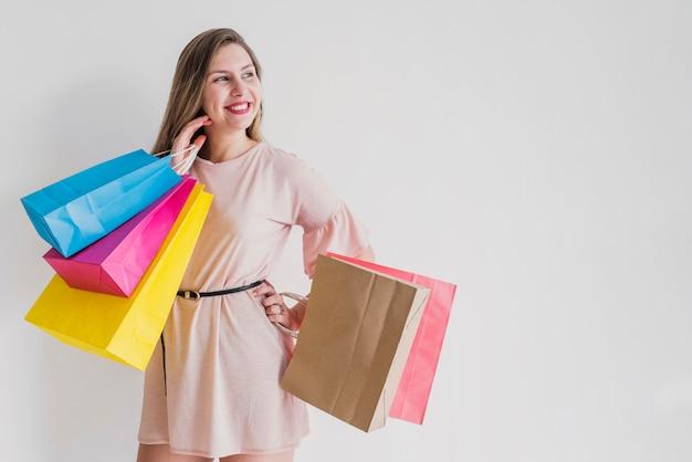 Glückliche frau, die mit hellen einkaufstaschen steht