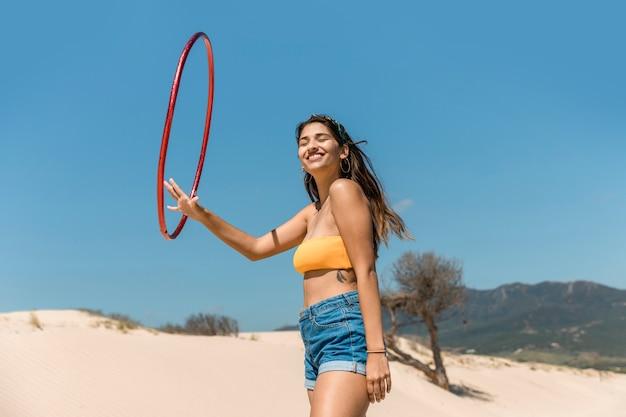 Glückliche frau, die mit hula band auf sand spielt