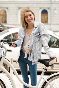 Glückliche frau, die mit ihrem fahrrad aufwirft