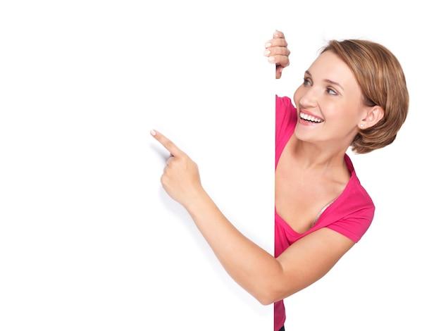 Glückliche frau, die mit ihrem finger auf banner lokalisiert auf weißer wand zeigt
