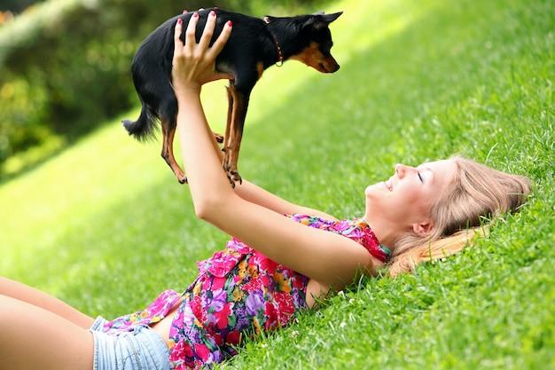 Glückliche frau, die mit ihrem hund auf dem gras liegt