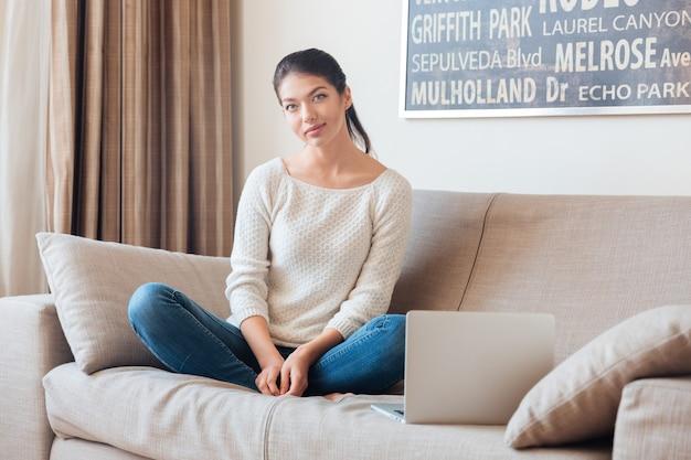 Glückliche frau, die mit laptop auf dem sofa sitzt und nach vorne schaut