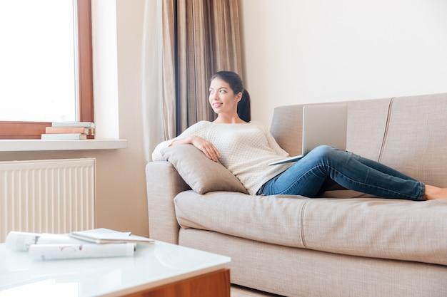 Glückliche frau, die mit laptop-computer auf dem sofa liegt und zum fenster wegschaut