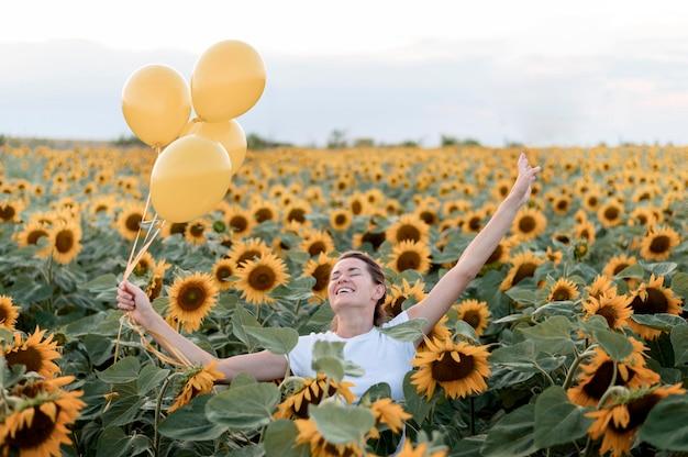 Glückliche frau, die mit luftballons aufwirft