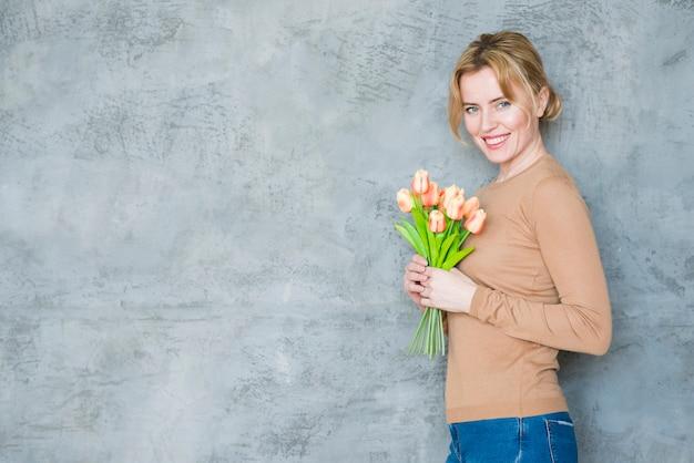 Glückliche frau, die mit tulpenblumenstrauß steht