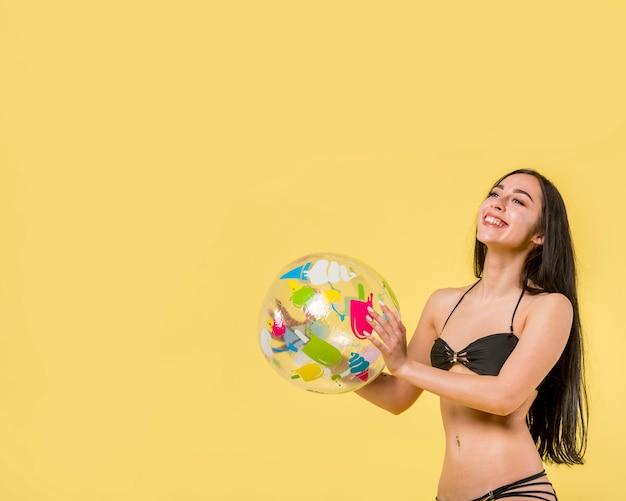 Glückliche frau, die mit wasserball spielt