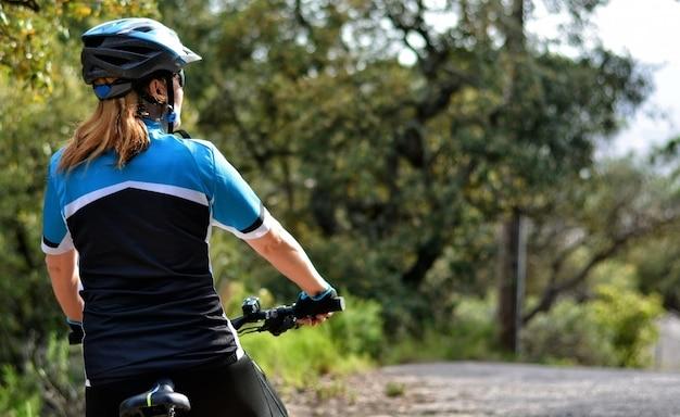 Glückliche frau, die mountainbike reitet