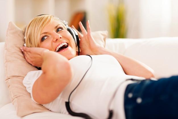 Glückliche frau, die musik auf sofa hört