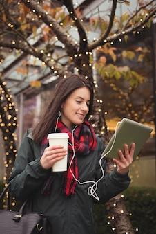 Glückliche frau, die musik auf tablette hört