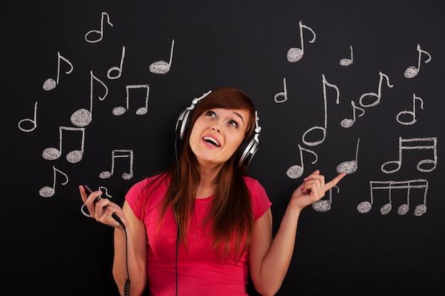 Glückliche frau, die musik durch kopfhörer hört