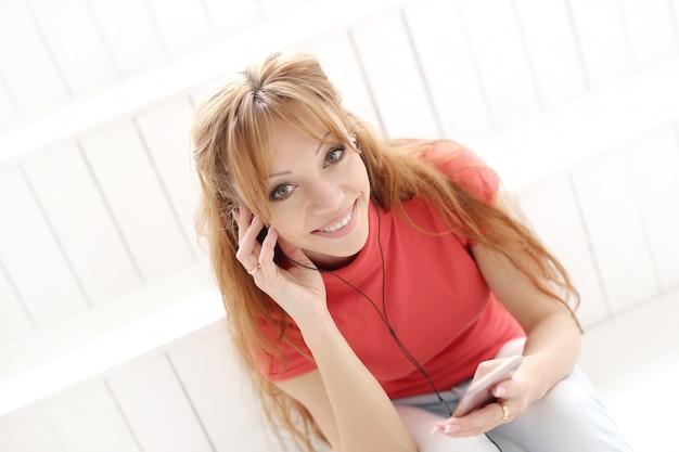 Glückliche frau, die musik mit kopfhörern hört