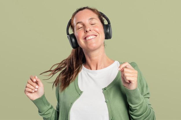 Glückliche frau, die musik über kopfhörer hört