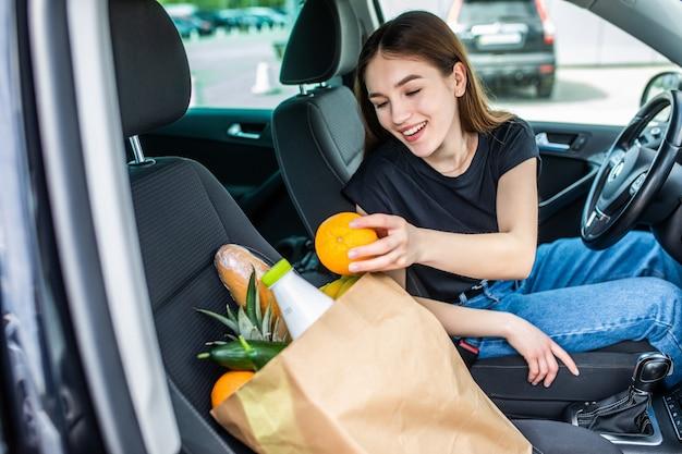 Glückliche frau, die nach dem einkaufen im supermarkt zum auto geht. hübsche erwachsene frau, die lebensmittel im auto hält
