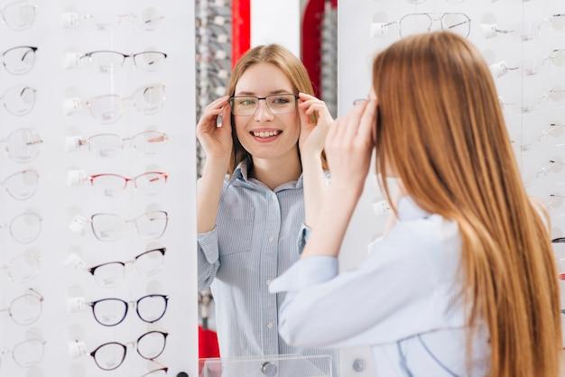 Glückliche frau, die nach neuen gläsern am optometriker sucht
