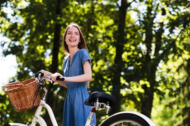 Glückliche frau, die nahe bei fahrrad steht