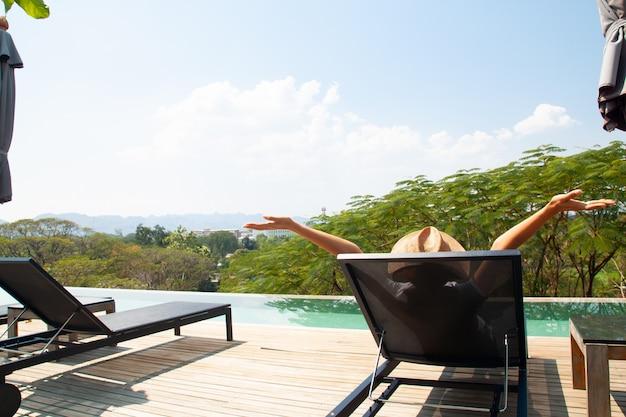 Glückliche frau, die nahe swimmingpool auf der dachspitze sich entspannt. sommerferienkonzept