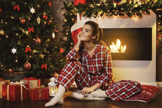 Glückliche frau, die neben dem kamin in den weihnachtsdekorationen sitzt
