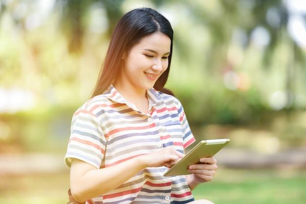 Glückliche frau, die notenauflagenunterhaltung und kommunikation der glücklichen studentingebrauchstechnologiebildung draußen hält