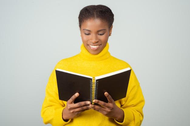 Glückliche frau, die notizblock studiert und lächelt