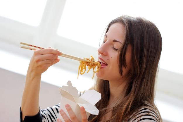 Glückliche frau, die nudeln isst