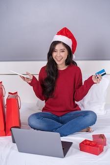 Glückliche frau, die online für weihnachtsgeschenk mit digitaler tablette und kreditkarte auf bett kauft