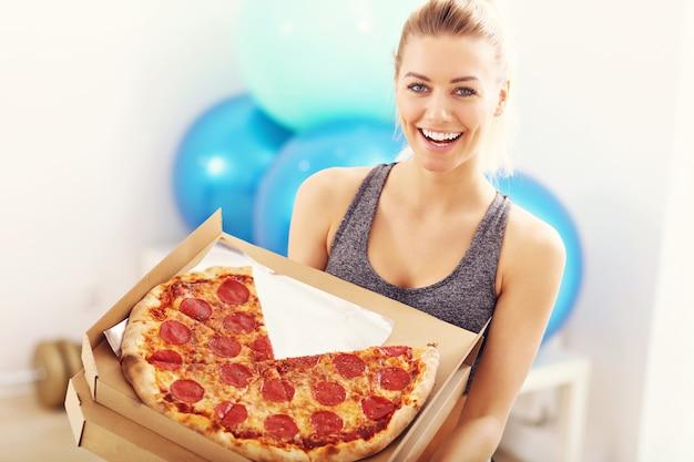 Glückliche frau, die pizza im fitnessstudio isst