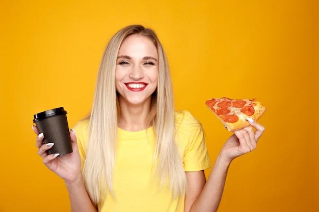 Glückliche frau, die pizza isst und eine tasse kaffee lokalisiert über der gelben wand hält.