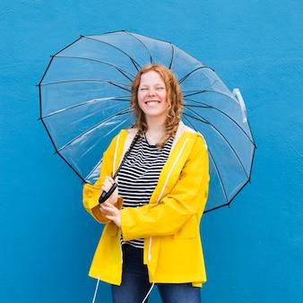 Glückliche frau, die regenschirm hält