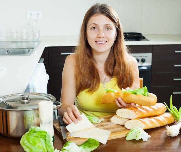 Glückliche frau, die sandwiche mit käse kocht