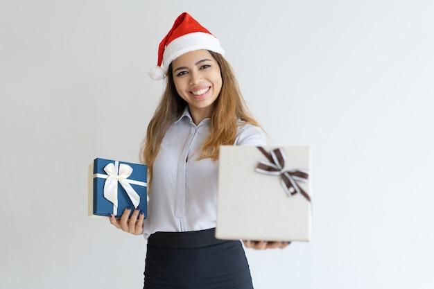 Glückliche frau, die santa claus-hut trägt und geschenkbox anbietet