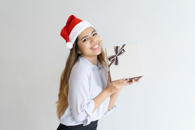 Glückliche frau, die santa claus-hut trägt und geschenkbox hält