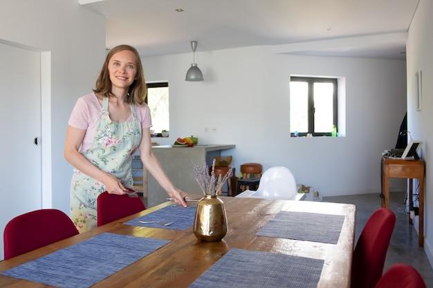 Glückliche frau, die schürze trägt und esstisch für familienessen zu hause dient. essen zu hause oder hausfrau konzept