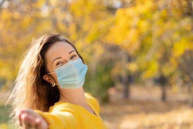 Glückliche frau, die schutzmaske im freien in einem park im herbst trägt.
