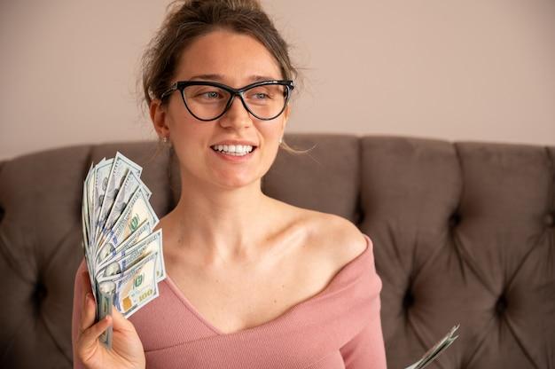 Glückliche frau, die schwarze brille trägt, die geld zeigt