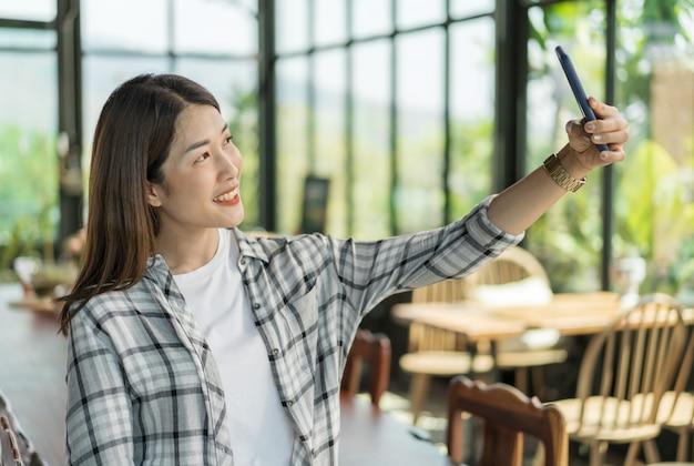 Glückliche frau, die selfie auf smartphone in einem café nimmt