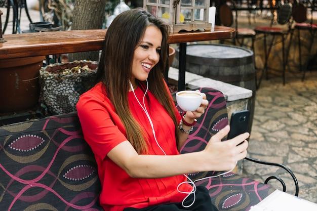 Glückliche frau, die selfie beim trinken von tasse kaffee nimmt