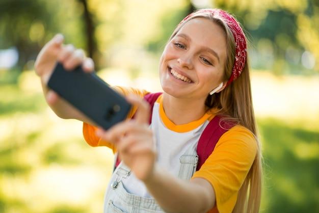Glückliche frau, die selfie draußen nimmt