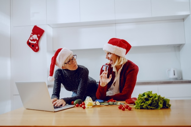 Glückliche frau, die sich auf küchentheke stützt und ihrer mutter kreditkarte zeigt. mutter, die tochter betrachtet und auf laptop tippt. beide haben weihnachtsmützen auf den köpfen. zeit für weihnachtseinkäufe.
