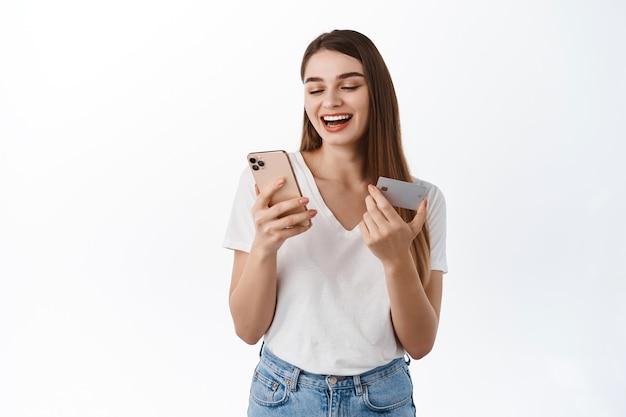Glückliche frau, die smartphone-bildschirm betrachtet und kreditkarte hält. mädchen lächelt, während sie für die online-shopping-bestellung bezahlt und über der weißen wand steht