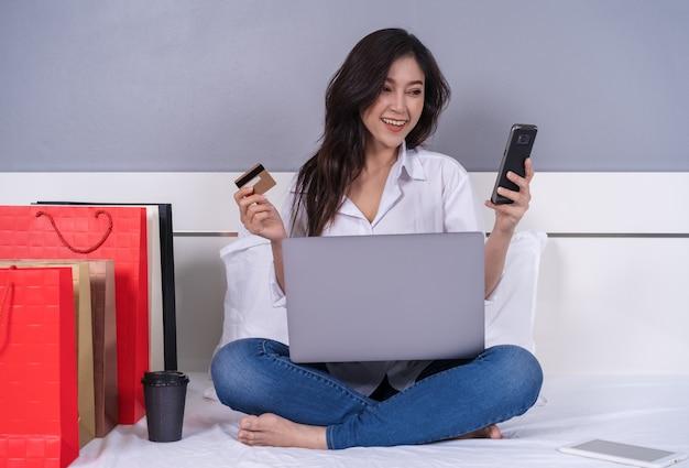 Glückliche frau, die smartphone für das on-line-einkaufen mit kreditkarte auf bett verwendet