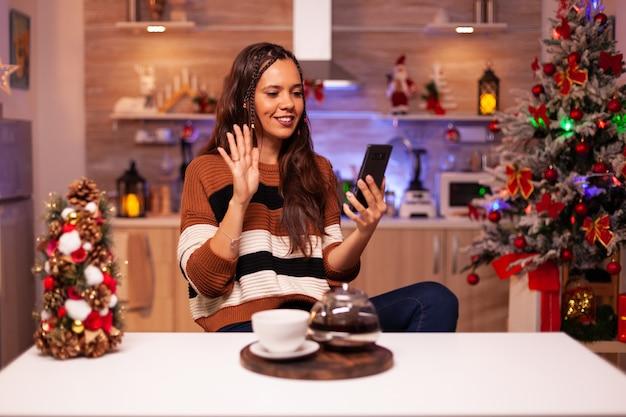 Glückliche frau, die smartphone für videoanruf hält
