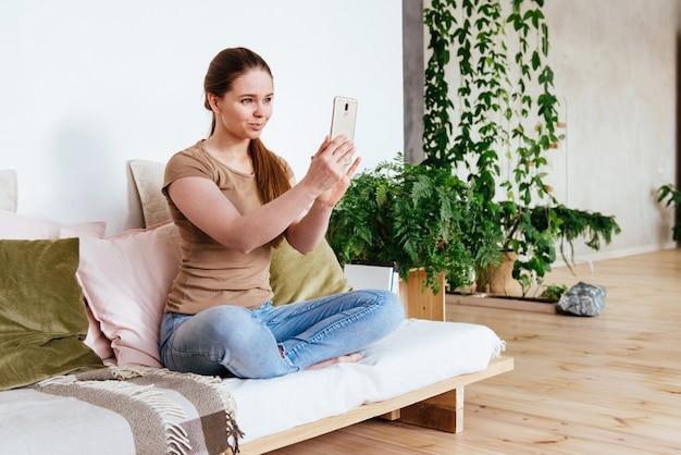 Glückliche frau, die smartphone für videoanruffreunde und -eltern verwendet, lächelndes mädchen, das zu hause auf sofa spaßgruß online durch webcam sitzt, der videoanruf macht