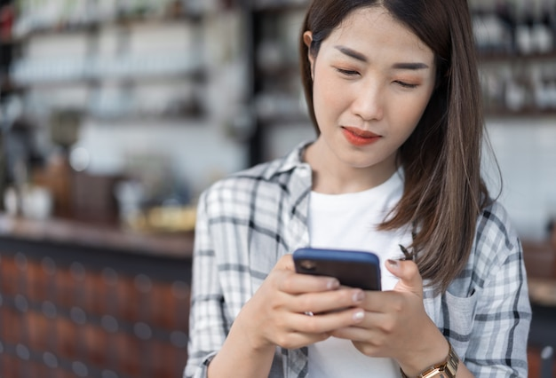 Glückliche frau, die smartphone im café verwendet