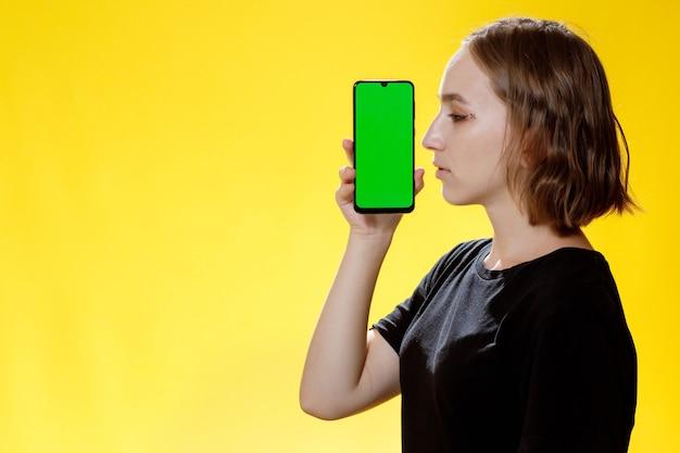 Glückliche frau, die smartphone mit grünem bildschirm, app für soziale netzwerke zeigt.