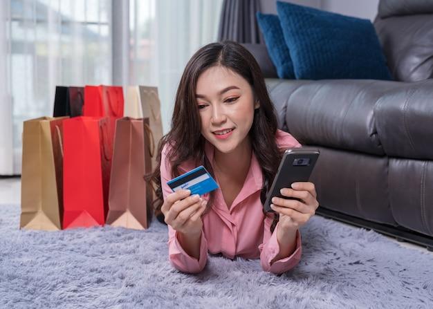Glückliche frau, die smartphone zum online kaufen mit kreditkarte im wohnzimmer verwendet