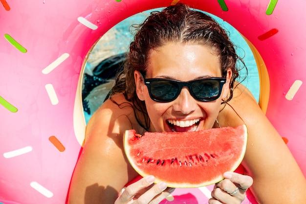 Glückliche frau, die sonnenbrille mit roter wassermelone trägt, genießen im schwimmbad mit rosa gummiring